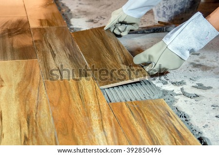 The man hand while using spacer for installing tiles.,Focus on the left hand side. construction work. - stock photo