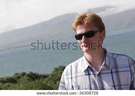 The man has vacation in Armenia on Sevan lake - stock photo