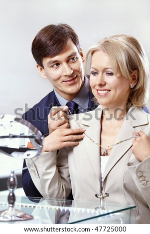 The man helps to put on an ornament to the woman - stock photo