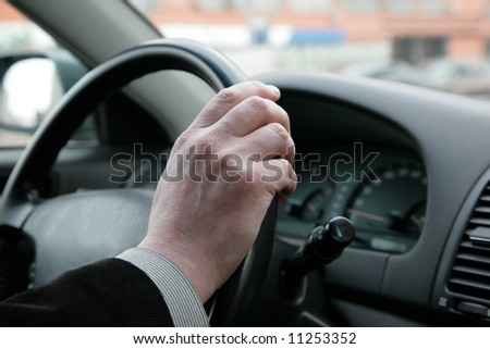 The man holds a steering wheel of the car