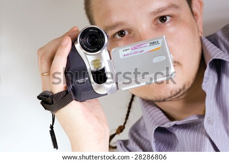The man holds an amateur digital videocamera - stock photo