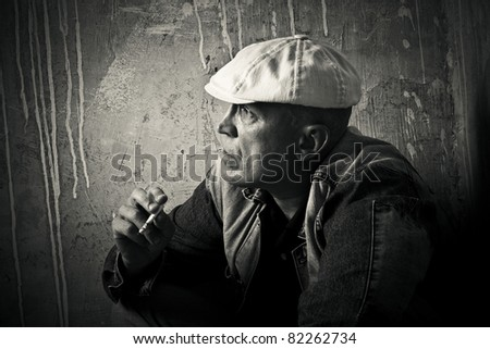 The man in a cap smokes a cigaret against a dirty wall - stock photo