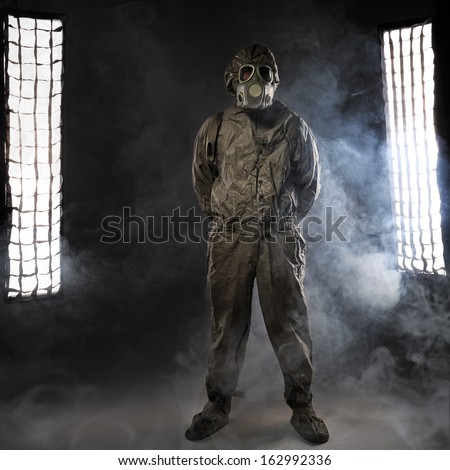 The man in a gas mask in smoke - stock photo