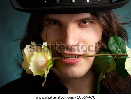 The man in a hat with a rose in a teeth - stock photo