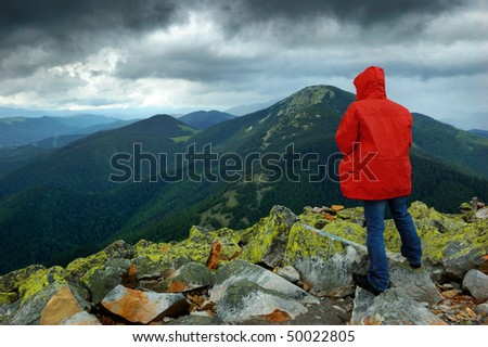 The man in a red jacket at mountain top in cloudy weather