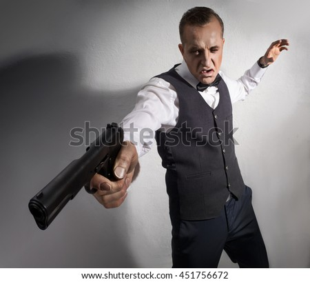 The man in a waistcoat with a butterfly on her neck, with the fear on the face of the gun shoots