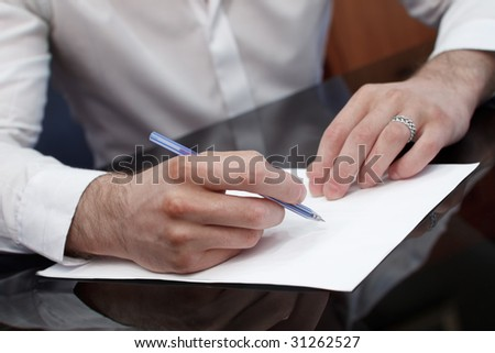 The man in a white shirt at the varnished black table was going to write on a paper blank leaf.  Limited focus on hand with pen.
