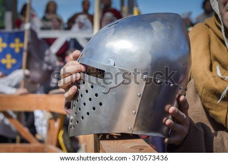 The man in ancient clothes holding a knight's helmet on the Knight Tournament  - stock photo