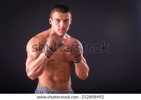 The man in boxing gloves. Young Boxer fighter over black background. Boxing man ready to fight.  Boxing, workout, muscle, strength, power - the concept of strength training and boxing - stock photo