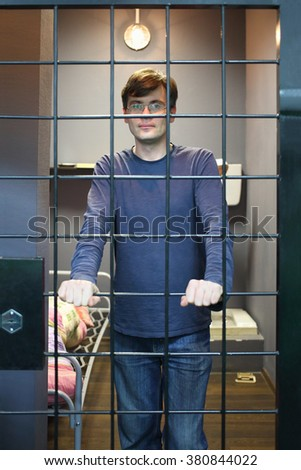 The man in glasses standing near lattice in a prison cell - stock photo