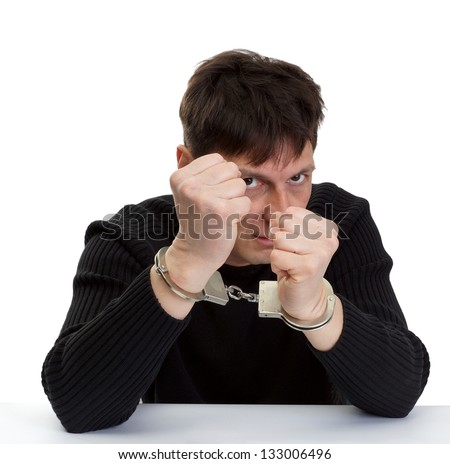 The man in handcuffs shakes fists. - stock photo