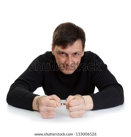 The man in handcuffs sits at a table and smiles - stock photo