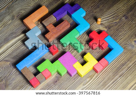 The man in the maze, flat lay. The concept of a business strategy, analytics, search for solutions, the search output. Labyrinth of colorful wooden blocks, tetris,top view. - stock photo