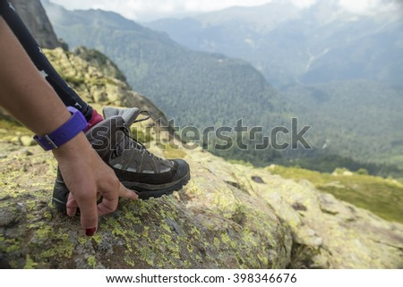 The man in the mountains showing his hand to unstick sole from hiking boots - stock photo