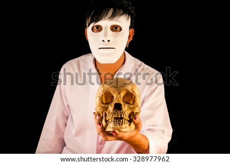 The man in white mask holding skull in hand on black background - stock photo