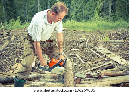 The man in wood saws a tree a chain saw,with a retro effect - stock photo