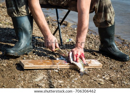 The man is cutting the fish outdoor