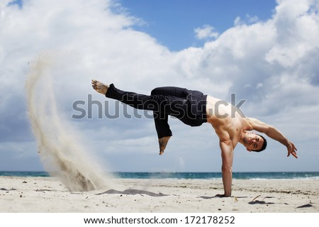 The man is doing capoeira on the beach - stock photo