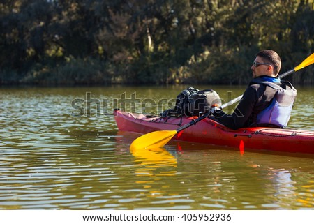 The man is kayaking on the river.  - stock photo