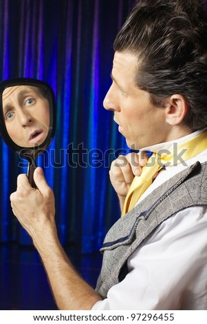 The man is looking at mirror - stock photo