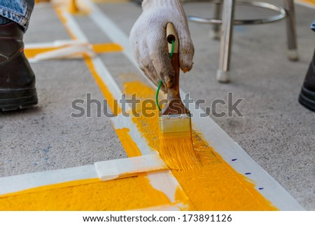 The man is painting the the yellow line on the concrete road - stock photo