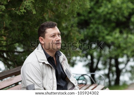 The man is resting in a summer park - stock photo