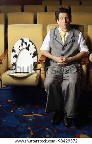 The man is siting indoors theater - stock photo