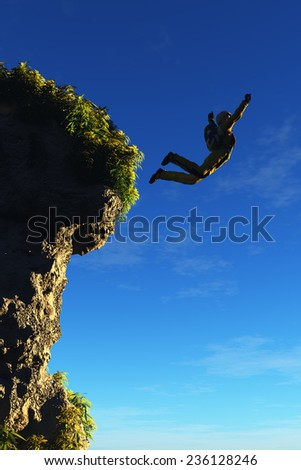 The  man jumps from a cliff. - stock photo