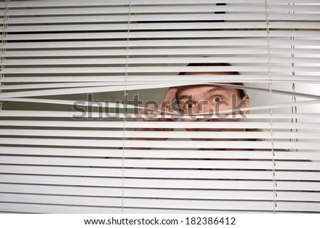 The man looks through jalousie - stock photo