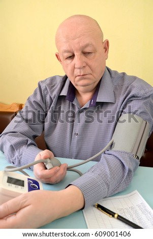 The man measures pressure by an electronic tonometer semiautomatic device