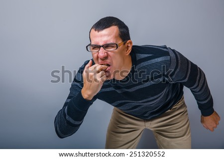the man of European appearance brunet in a sweater put his fingers in his mouth on a gray background, nausea, vomiting - stock photo