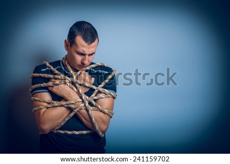 the man of European appearance brunet tied with a rope hung his head on a gray background cross process - stock photo