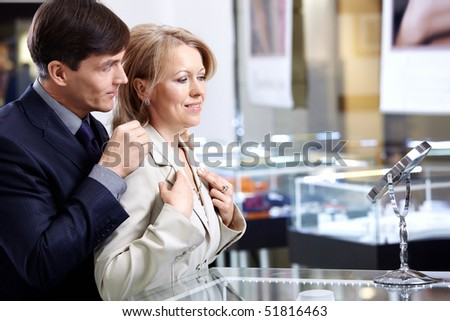 The man of middle age helps the woman to put on a jewel - stock photo