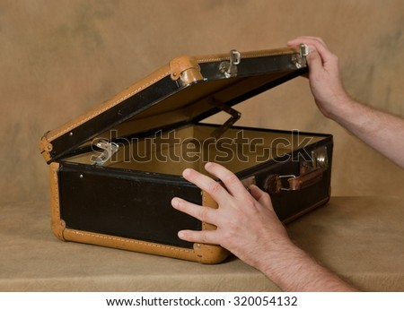 The man opens the suitcase - stock photo