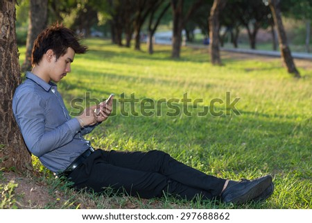 The man playing mobile phone under a tree.