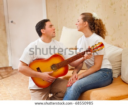 The man plays a guitar for the girl, an interior - stock photo