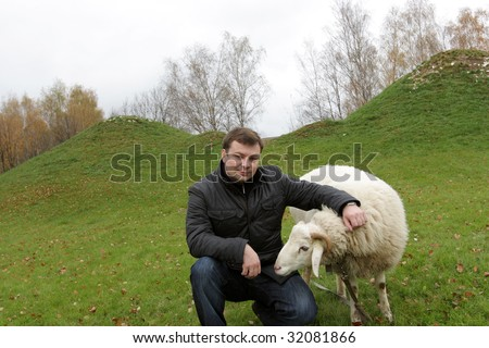 The man poses with white sheep on lawn - stock photo