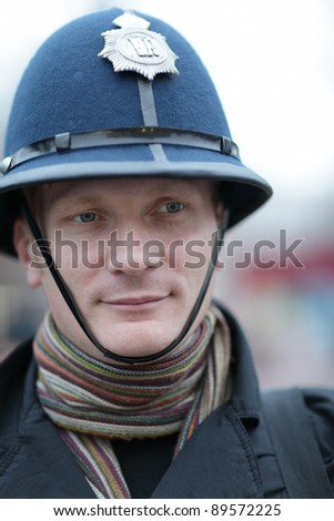 The man posing in british police hat - stock photo