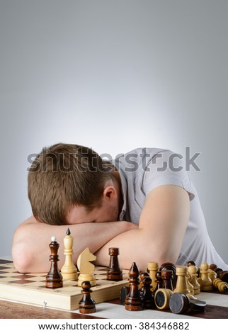 The man put his head on his folded hands on the chessboard - stock photo