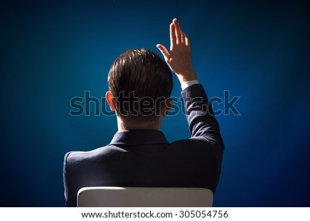 The man raised his hand up and wants to ask a question - stock photo