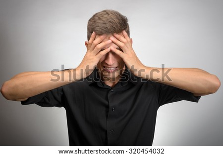 The man really tired, he covered his face with his hands. Gray background - stock photo