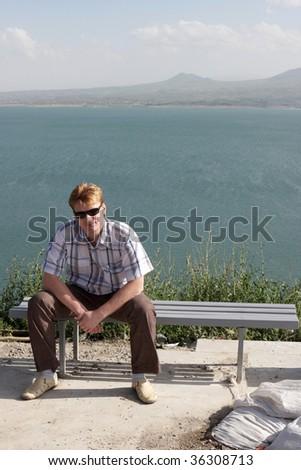 The man resting on bench, Sevan, Armenia - stock photo