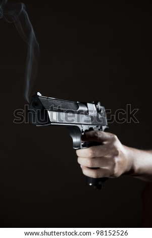 The man's hand holds a pistol, from a trunk there is a smoke - stock photo