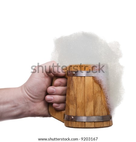 The man's hand holds big wooden beer mug collected from plates with froth. Isolated on white [with clipping path]. - stock photo