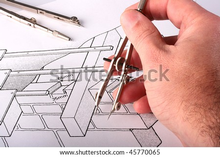 The man's hand holds the measuring drawing tool over the drawing. - stock photo