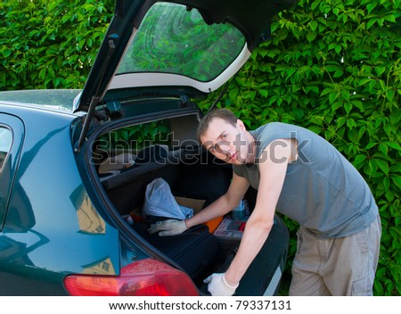 The man searches for something in a luggage carrier - stock photo