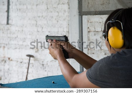 the man shooting with gun  - stock photo
