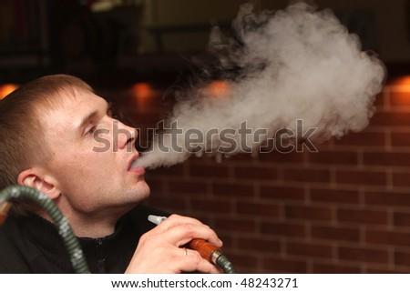 The man smoking shisha at arabic restaurant - stock photo