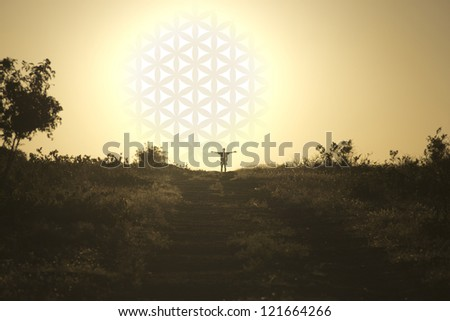 The man standing with his hands up near the setting sun with flower of life - stock photo