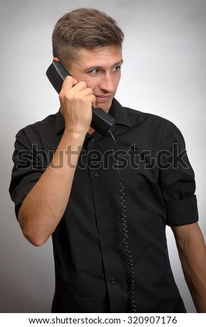 The man talking on a wired phone. On a gray background. - stock photo